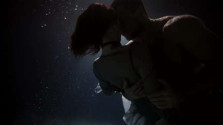 man and woman are embracing underwater in darkness Foto de archivo