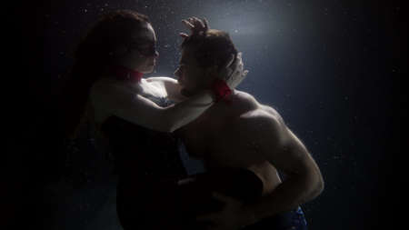 mysterious lovers are hugging and floating underwater, slow motion shot, woman in bdsm suit