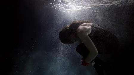 female figure in dark depth underwater, woman is floating in water of sea or ocean Foto de archivo