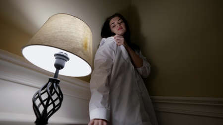 pensive and sad young woman dressed white shirt is leaning on wall in room and lowering Foto de archivo