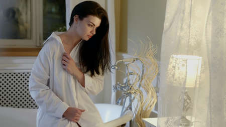 tender brunette woman in luxury bathroom, sitting on bathtub, light interior Foto de archivo