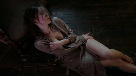 excited woman in lingerie is lying on floor in room and stroking her body, top view