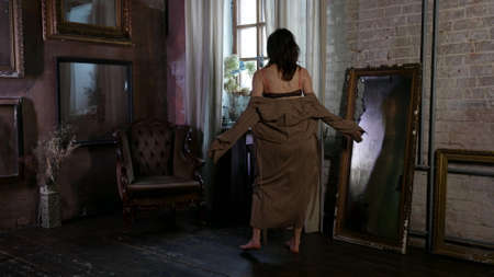 slender housewife dressed lingerie and silk gown is dancing alone in living room of big house Foto de archivo