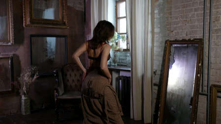 sexy lady dressed erotic lace lingerie is posing in front of mirror and looking herself