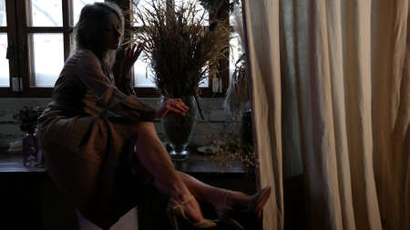 romantic adult woman is resting at home, sitting on windowsill and stroking her leg