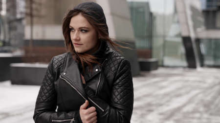 young brunette lady is walking alone in city at cold winter day, wrapping in leather jacket