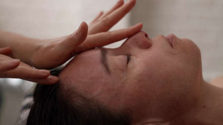 face massage for relax and rejuvenate, closeup view in beauty salon, female therapist is stroking face Foto de archivo