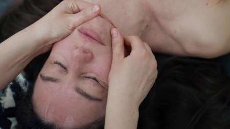 aesthetician is doing face massage for middle aged female patient in beauty salon Foto de archivo