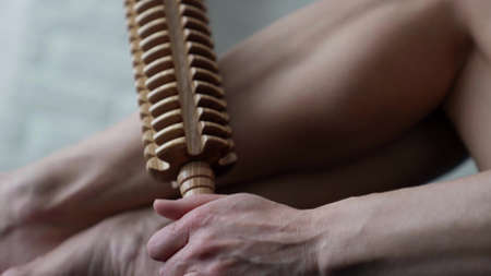 health and beauty treatments, woman is using wooden roller for massaging legs