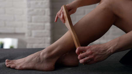 adult woman is massaging her legs by wood plate, closeup view, massaging muscles and skin Foto de archivo