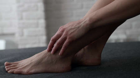 female feet on bed or couch, woman is stroking her skin by fingers, closeup view