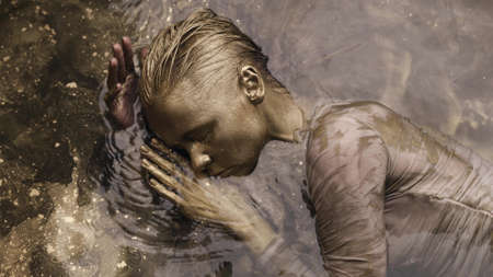unusual fashion shot with tender woman covered golden paint in water, moving slowly