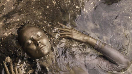 art and fashion shot of young woman with skin and hair covered by golden shiny dye in shallow