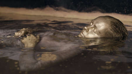 ancient goddess with golden skin is floating in water, closeup portrait of female face Standard-Bild