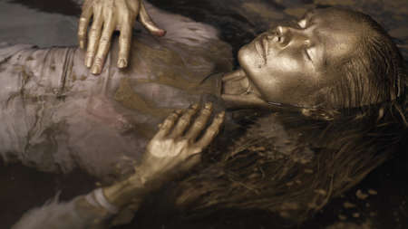 fashion model covered by gold paint in water, posing with closed eyes, body and face art Standard-Bild
