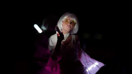 slim woman with blonde wig on head is dancing in dark room, lighting on her body by lamps Standard-Bild