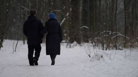 happy long marriage, elderly spouses are walking together in winter park, rear view of pair