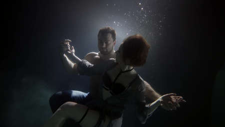 muscular man is holding graceful woman in hugs underwater, tenderness and love of young people