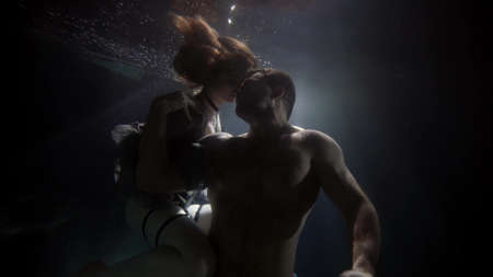 caresses of loving couple inside water of swimming pool, underwater shot, romantic and sexuality Standard-Bild