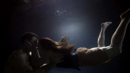 man and woman are kissing underwater, slow motion shot, moving to each other and back