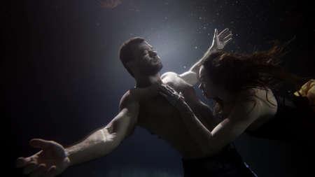 mermaid is stroking brawny body of sunken man, underwater shot in dark deepness Standard-Bild