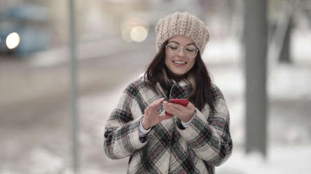 young woman is walking in city and viewing social nets in smartphone, chatting online and smiling