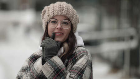 portrait of funny young townswoman at winter in city, pretty face grimacing, looking at camera