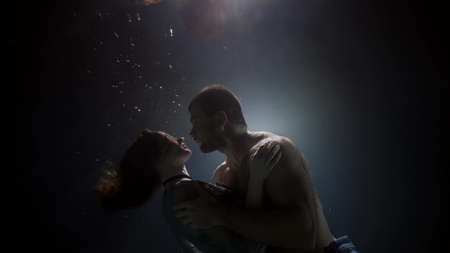 handsome man is embracing his girlfriend underwater, love and passion of loving couple
