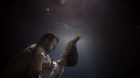 brawny man and slender woman are embracing underwater, dark depth and stream of light, romantic and passion