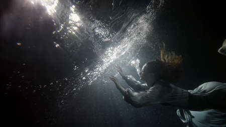graceful young woman is swimming underwater, touching mirror surface of pool, subaquatic shot
