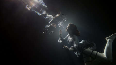 young woman is floating underwater and touching reflection in surface, magic slow motion shot in pool