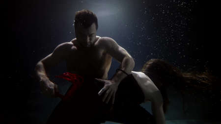 man is whipping with whip his girlfriend floating underwater, bdsm sex practice in swimming pool