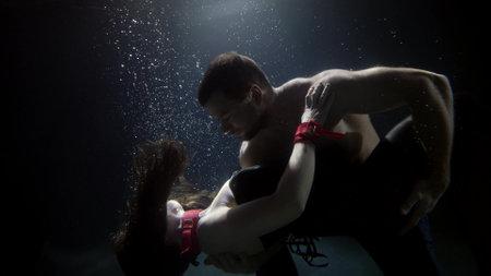dancing pair inside water of swimming pool, man is hugging slender woman and looking at camera