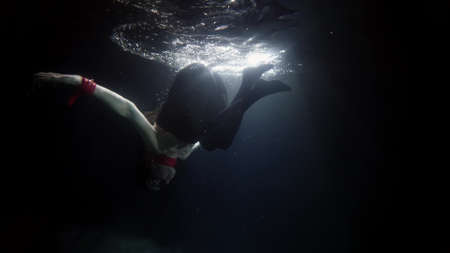 woman dressed in clothes is swimming underwater, diving into dark water