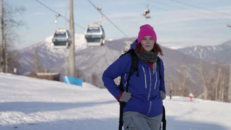 sporty woman in ski resort at sunny winter day, portrait against funicular with skiers and snowboarders