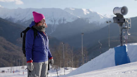 portrait of woman in mountain city with ski resort at winter sunny day, skier or snowboarder