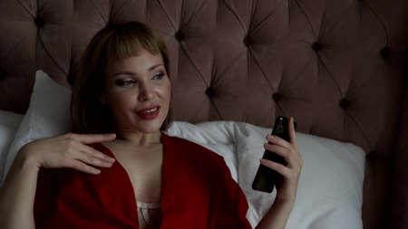 pretty busty blonde in erotic silk gown is listening to voice message by smartphone in bedroom, portrait Standard-Bild