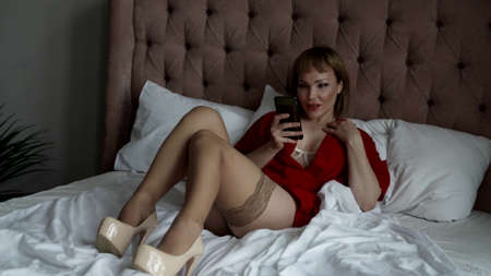 sexy lady in bedroom at weekend, lying on bed and using smartphone, viewing social nets
