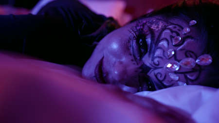 closeup portrait of woman with artistic stage makeup lying in bedroom at night, face with crystal Standard-Bild