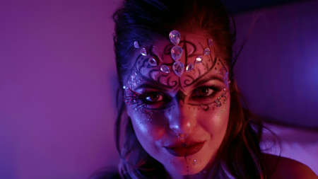 crazy lady with extravagant makeup is grimacing to camera in dark room at night, closeup of face Standard-Bild