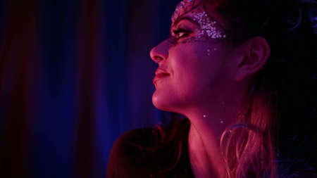 beautiful woman with theatrical stage makeup is posing in darkness, flirting and winking to camera Standard-Bild