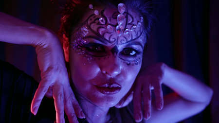 beautiful woman with artistic makeup is dancing hypnotically in darkness, closeup of face