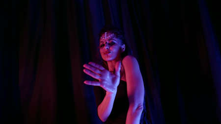 playful woman is dancing exotic dance in darkness in bedroom, artistic makeup with crystals on face