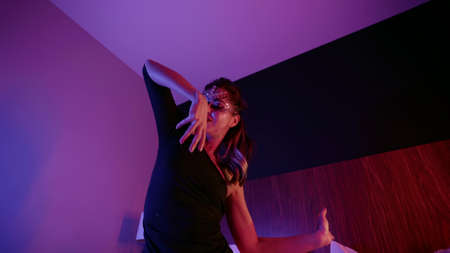 extravagant woman with stage make-up is dancing on bed in hotel room at night, medium portrait shot