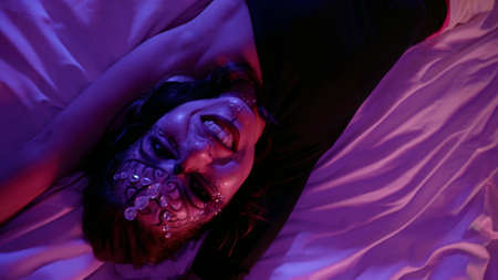 crazy eccentric woman with fashion makeup with crystals on face is lying on bed in darkness, emotional portrait