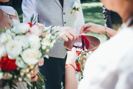 fingers put together: Groom wearing wedding ring on finger of bride Stock Photo