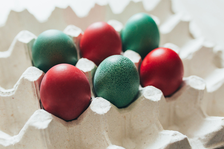 Easter eggs of different colors in tray background