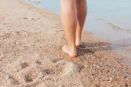 Woman walking on the beach leaving footprints in the sand