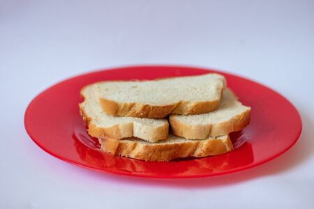 A loaf of bread lies on a red plate on a white background