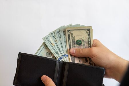 Pay with dollars. Get dollars out of your wallet. Dollar bills on a white background with a wallet 写真素材